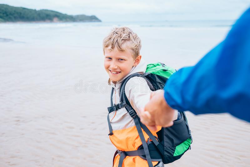 De reiziger van de Backpackerjongen neemt zijn vaderhand op de oceaankust royalty-vrije stock afbeelding