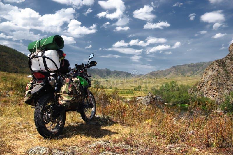 De reiziger van motorfietsenduro met koffers in bergvallei op de achtergrond van de rotsachtige heuvels stock fotografie