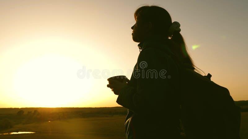 De reiziger van de silhouetvrouw, tribunes bovenop een heuvel het drinken koffie in glas van thermosflessen het toeristenmeisje d stock afbeeldingen