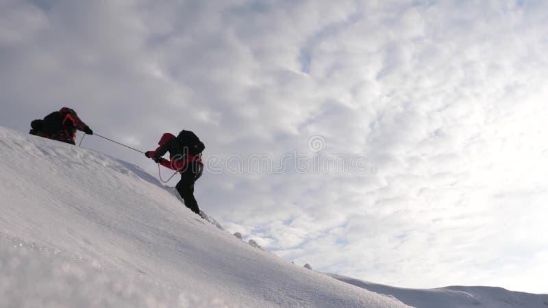 De reizigers beklimmen kabel aan hun overwinning door sneeuwhelling in een sterke wind De toeristen in de winter werken samen als stock afbeelding