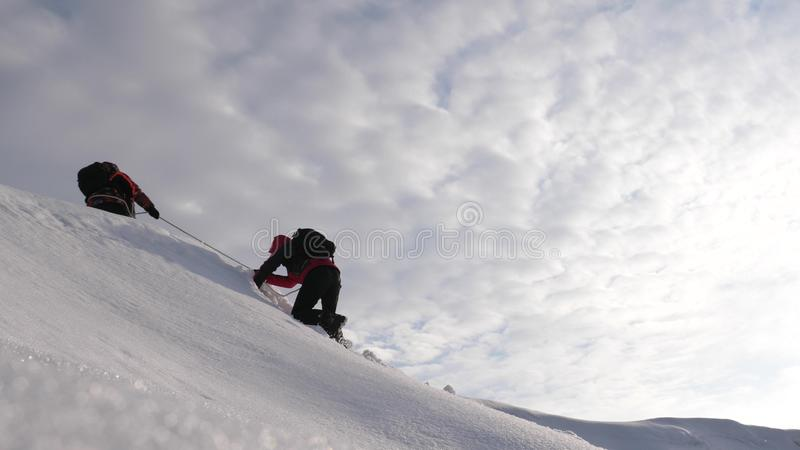 De reizigers beklimmen kabel aan hun overwinning door sneeuwhelling in een sterke wind De toeristen in de winter werken samen als stock foto