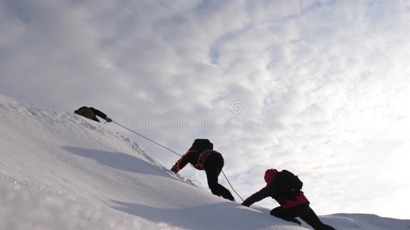 De reizigers beklimmen kabel aan hun overwinning door sneeuwhelling in een sterke wind De toeristen in de winter werken samen als stock foto's