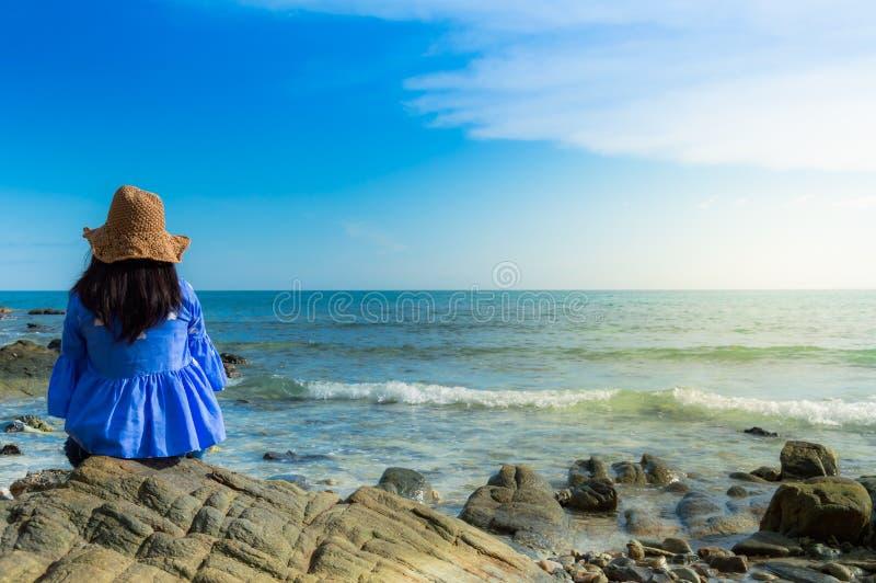 De reizigers kunnen op de rots bij het strand zitten en ontspannen royalty-vrije stock afbeeldingen