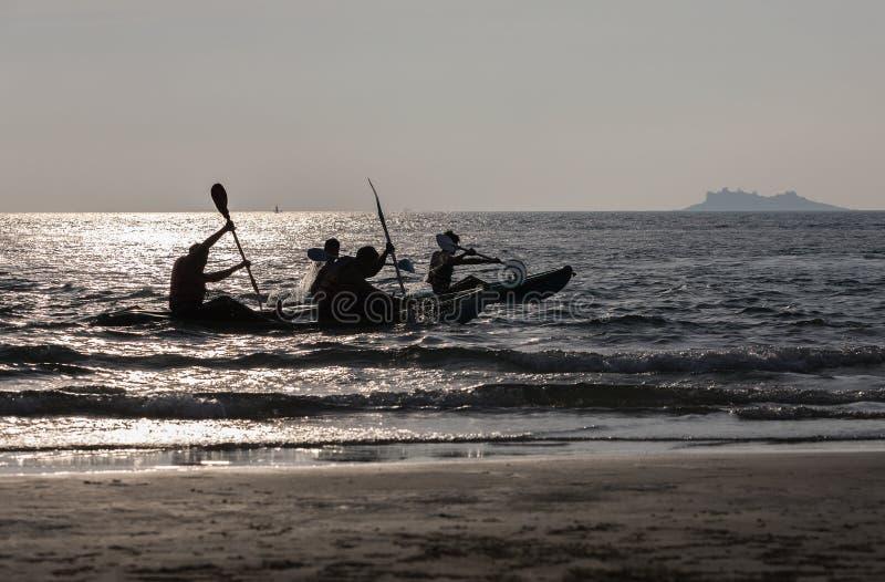 De reizigers spelen kajaksrace in de kust en nemen een foto op het strand stock foto
