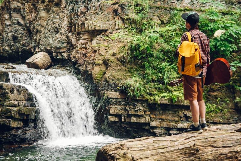 De reizigersmens met een rugzak en een gitaar bevindt zich op een boomstam van een boom tegen een waterval Ruimte voor uw sms-ber royalty-vrije stock afbeelding