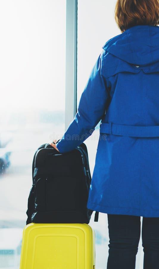 De reizigerstoerist met gele kofferrugzak bevindt zich bij luchthaven op groot venster als achtergrond, meisje in helder jasjewac stock foto's