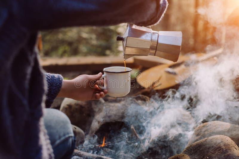 De reizigersvrouw in blauwe sweater giet zich hete drank dichtbij in bergen aan vuur, die na trekking ontspannen stock foto's