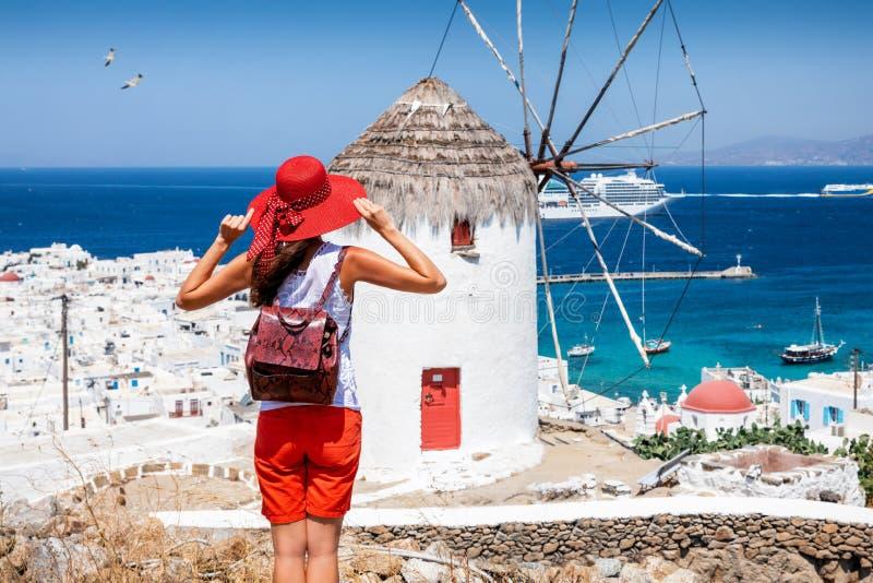 De reizigersvrouw geniet van de mening aan een traditionele Griekse windmolen in Mykonos stock foto
