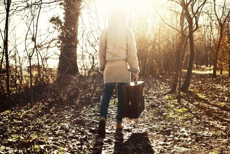 De reizigersvrouw volgt het licht van hoop in het bos royalty-vrije stock foto
