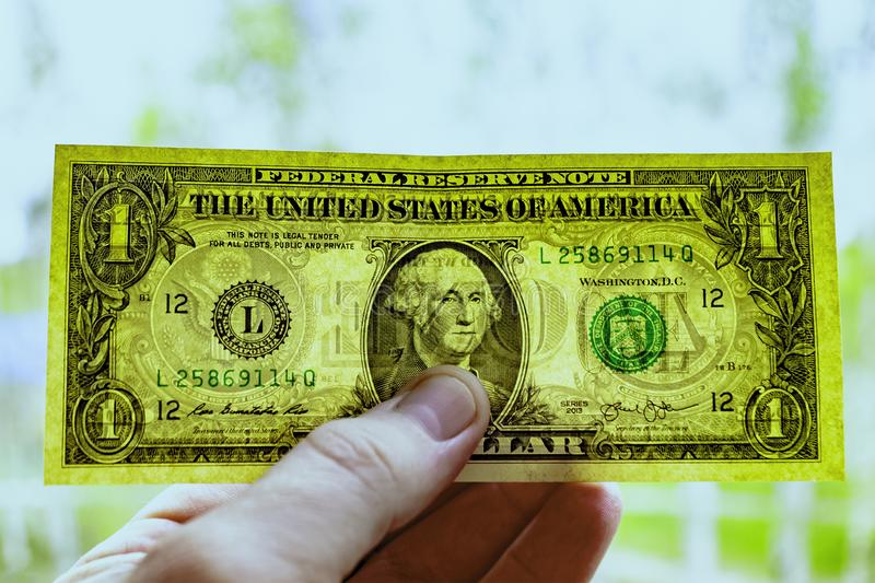 De rekening is één dollar voor ontruiming in de hand van een mens, tegen de achtergrond van aard royalty-vrije stock afbeeldingen