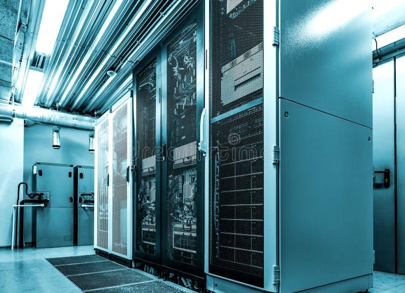 De rekken van de Datacenterserver met netwerkcomputers in neon het blauwe stemmen Zaal met binnen verscheidene van centrale verwe stock foto