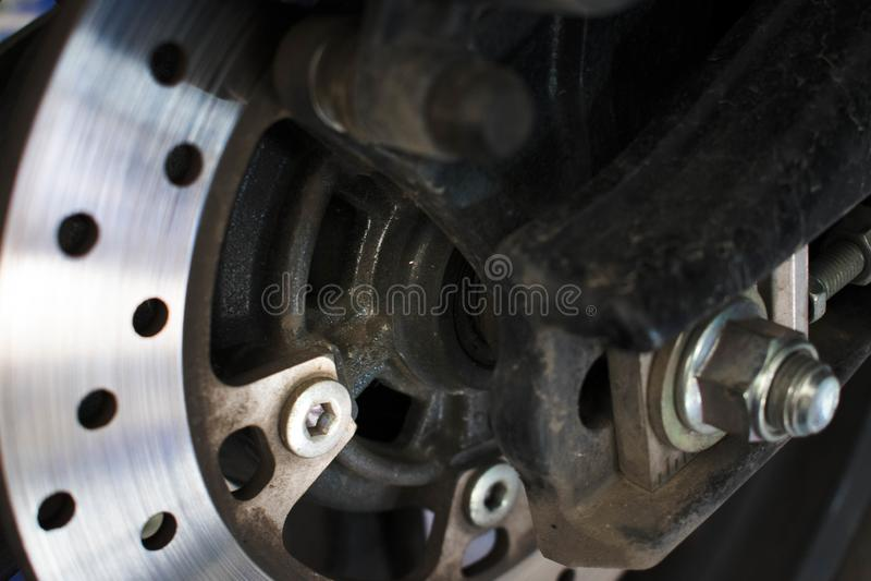 De Remmotorfiets en wiel van de close-upschijf met olievlek stock afbeelding