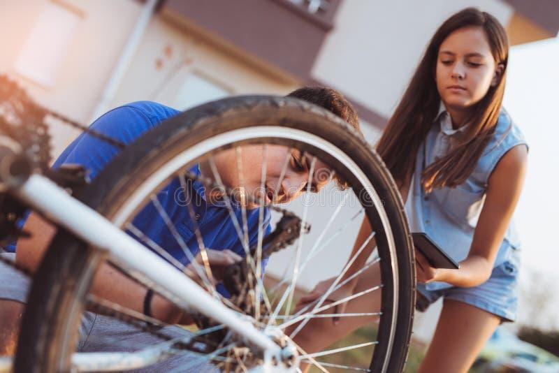 De reparatieband van de tienerjongen op fiets royalty-vrije stock afbeelding