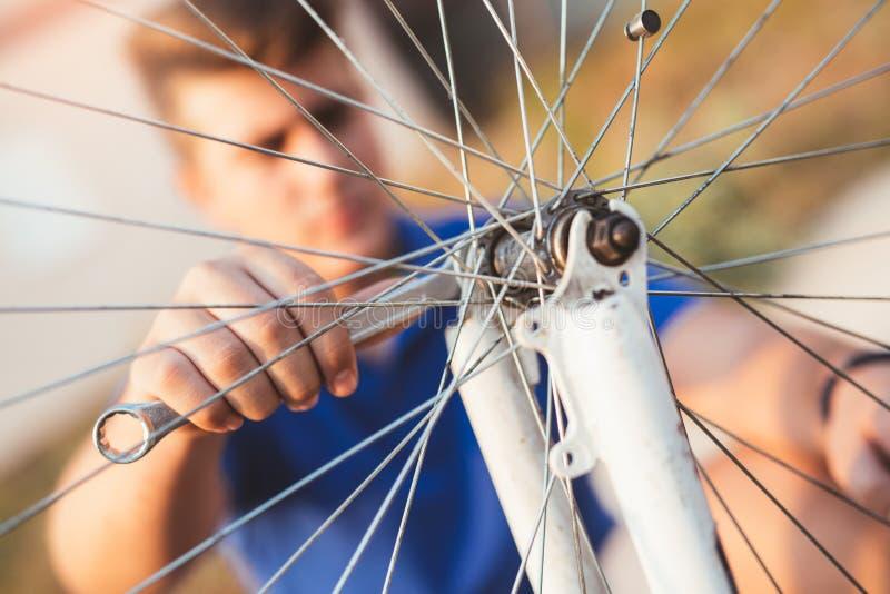 De reparatieband van de tienerjongen op fiets royalty-vrije stock foto