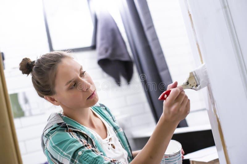 De reparaties van het huis Een geconcentreerde vrouw schildert in wit de ingang aan de badkamers met een borstel en kan, die zij  stock foto's