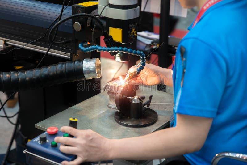 De reparatievorm van het arbeiderslassen en matrijzendeel door de machine van het Laserlassen royalty-vrije stock fotografie