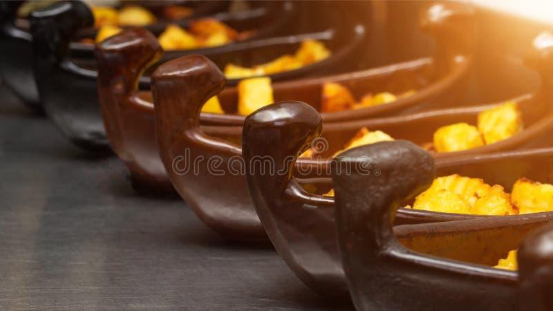 De restaurantschotel van een boot met aardappels in een gouden korst braadde in een frituurpan close-up, zon royalty-vrije stock afbeelding
