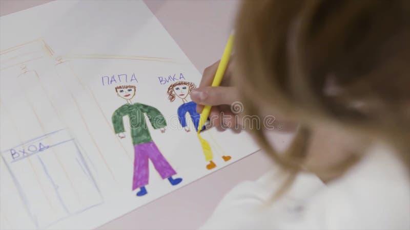 De retour au-dessus de la vue d'épaule d'un petit enfant blond avec les cheveux bouclés dessinant une personne avec les crayons c images stock
