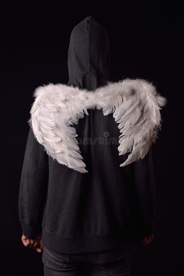 De retour d'un jeune homme avec le hoodie noir et le blanc a fait varier le pas des ailes images stock