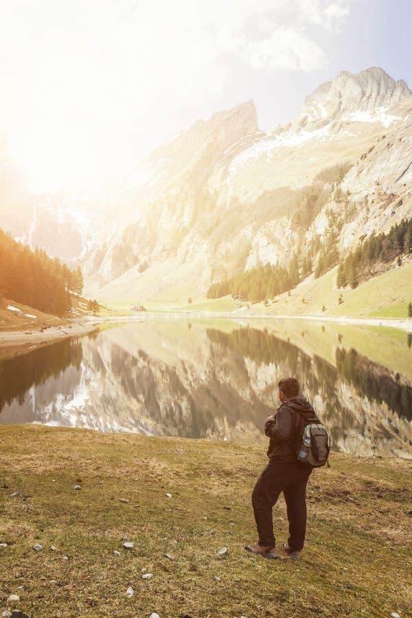 De retour du randonneur avec le sac à dos qui observant au lac et au mountai photo stock