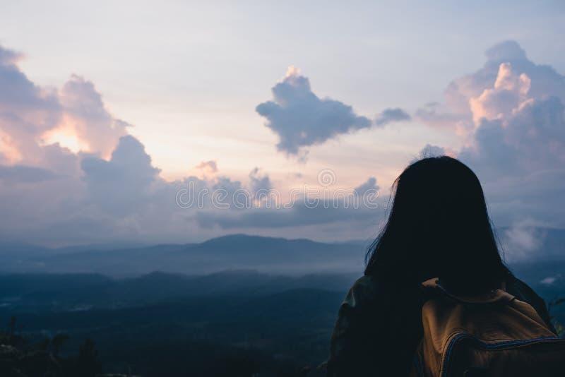 De retour du randonneur regardant la vue dans le temps de montée du soleil au sommet de la montagne Vue de matin de nature image libre de droits