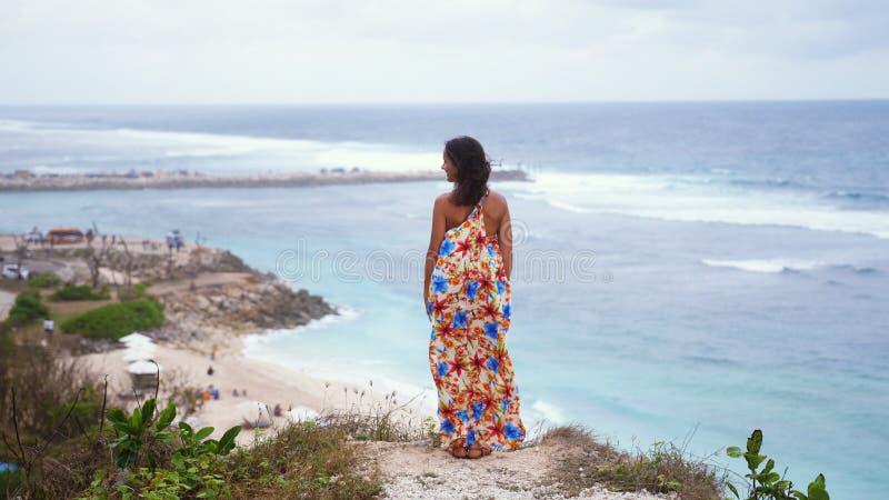 De retour de la vue de la jeune femme réfléchie de brune avec de longs cheveux portant la longue robe se tenant sur une roche à c photographie stock