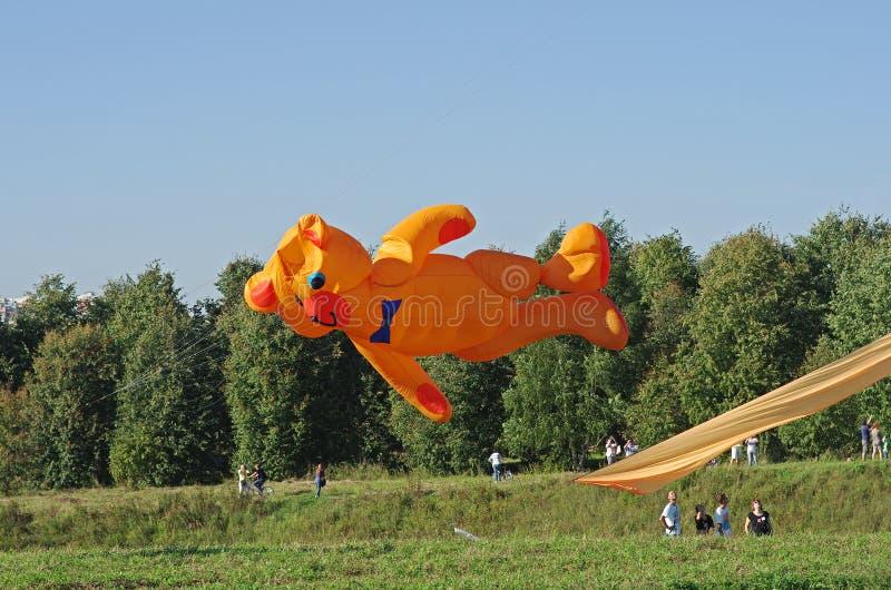 De reusachtige sinaasappel draagt vlieger bij het vliegerfestival in het Park Tsaritsyno in Moskou royalty-vrije stock afbeeldingen