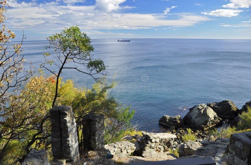 De reusachtige zwarte stenen liggen in een blauwe overzees op een blauwe hemel met witte wolken royalty-vrije stock foto's