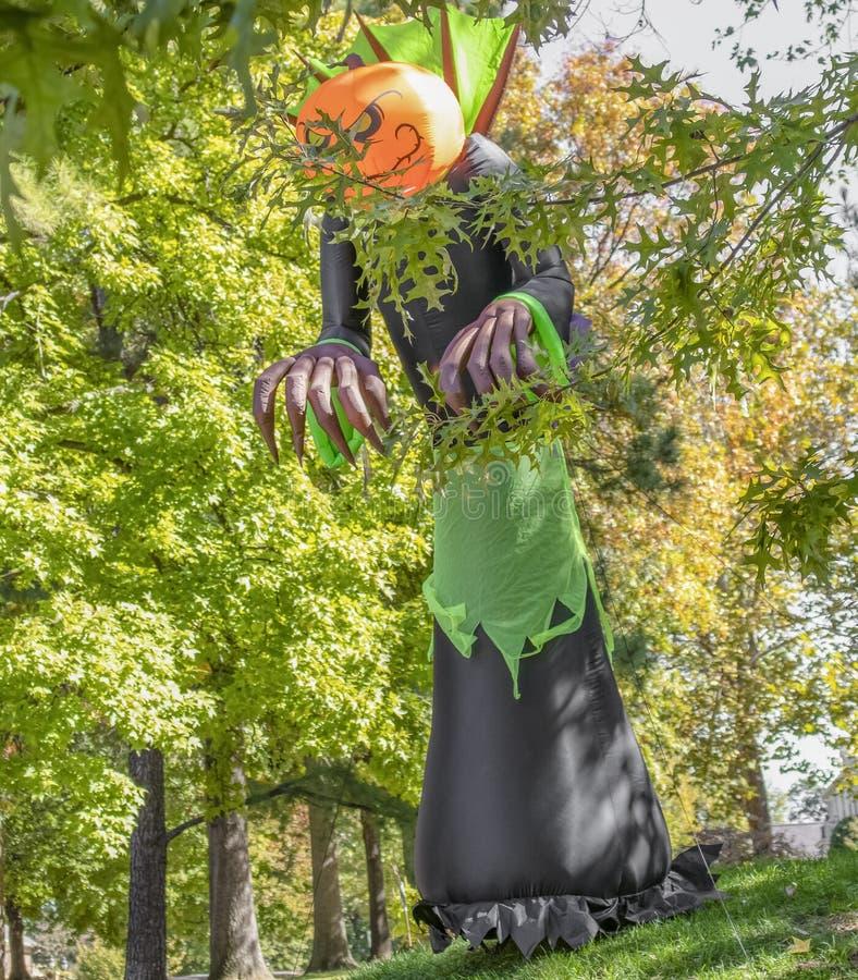 De reuzepompoen leidde de enge die decoratie van ontploffinghalloween wordt gebonden om status onder lange bomen in een woonbuurt stock foto's