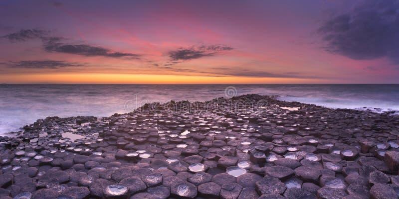 De Reuzeverhoogde weg van ` s in Noord-Ierland bij zonsondergang stock afbeelding