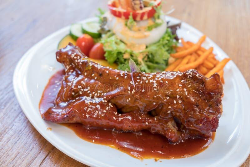 De ribben van het barbecuevarkensvlees met gebraden bataten en gemengde salade op witte plaat royalty-vrije stock afbeeldingen