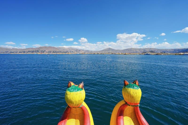 De rietboot op het Meer Titicaca met mooie blauwe hemel En het rieteiland is vooraan, niet ver weg royalty-vrije stock fotografie