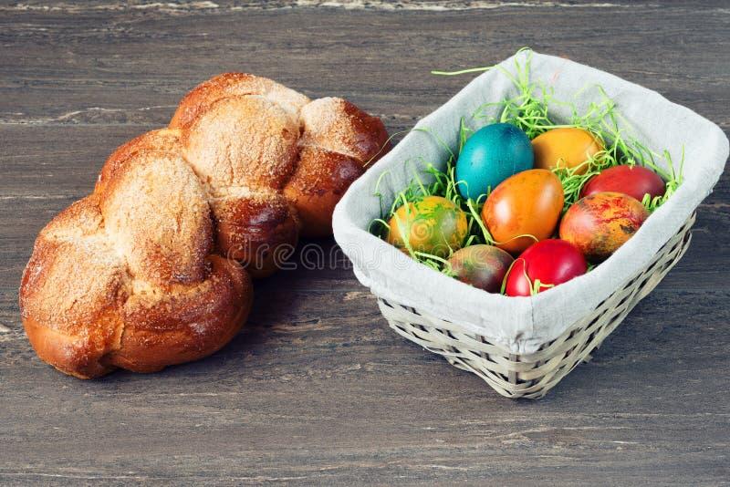 De rieten mand van Pasen met gekleurde eieren en Pasen-brood op grijze houten raad royalty-vrije stock foto's