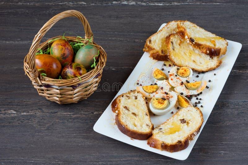 De rieten mand van Pasen met gekleurde eieren en gesneden Pasen-brood in witte plaat op grijze houten raad stock afbeelding