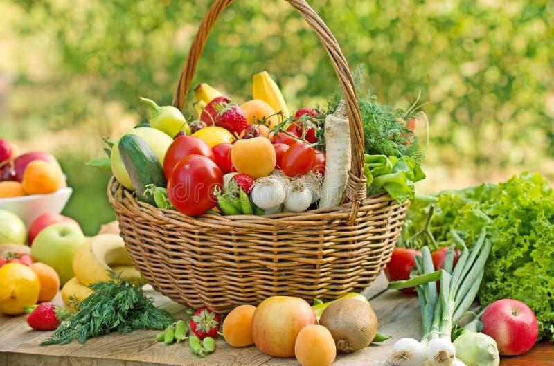 De rieten mand is volledig met vruchten en groenten stock fotografie