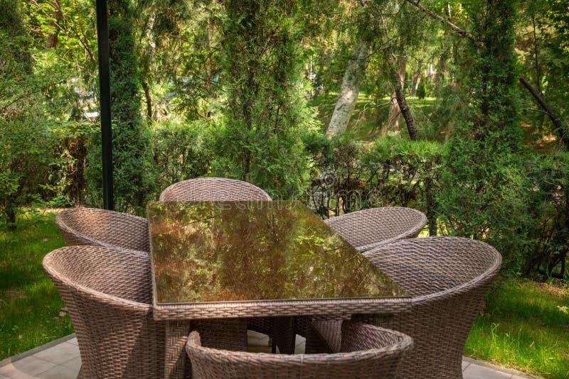De rieten stoelen en de lijst zijn in de tuin dichtbij bomen stock afbeelding