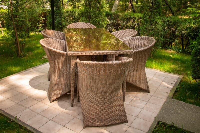 De rieten stoelen en de lijst zijn in de tuin dichtbij bomen royalty-vrije stock foto's