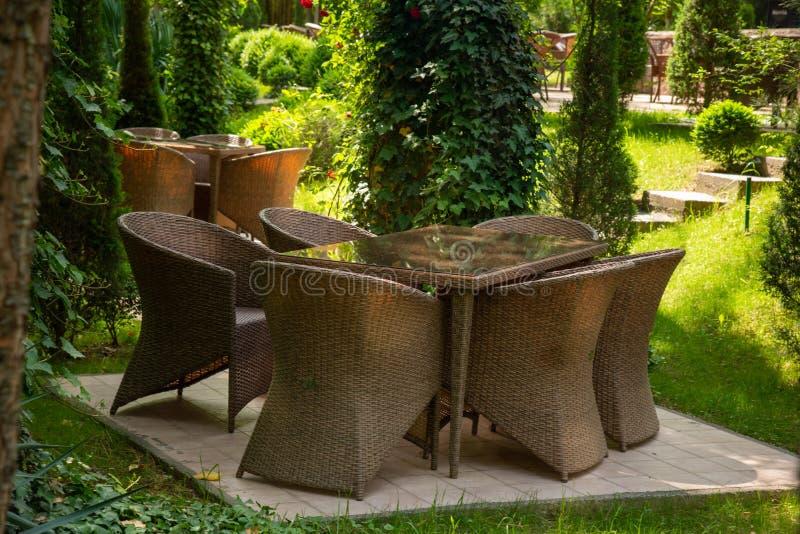 De rieten stoelen en de lijst zijn in de tuin dichtbij bomen royalty-vrije stock afbeeldingen