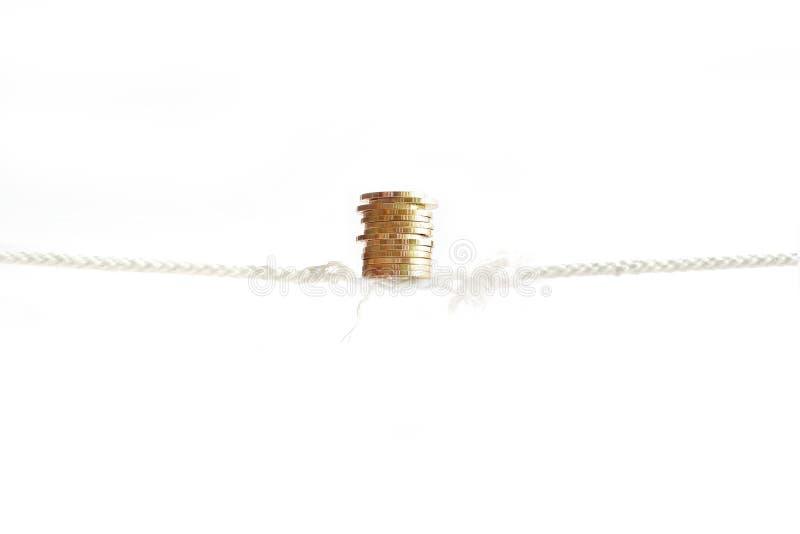 De rij van gouden muntstukken is aanhoudend in evenwicht brengend op bijna afwezige kabel stock foto