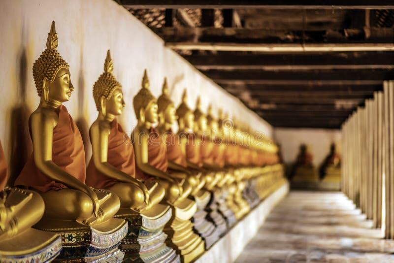 De rij van de gouden zitting van meditatieboedha komt voor de standbeelden binnen gang in Wat Phutthaisawan, Si Ayutthay van Phra royalty-vrije stock foto's