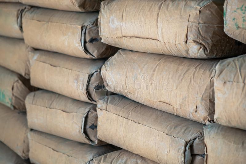 De rij van Ruwe Bruine Cementzak legt Stapel in de Bouwwerkzaamheidplaats stock afbeeldingen