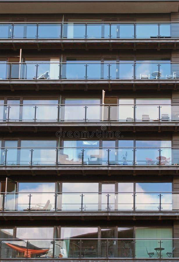 De rijen van flats in een groot modern gebouw met glasbalkons en openluchtmeubilair en hemel dachten in de vensters na royalty-vrije stock afbeeldingen