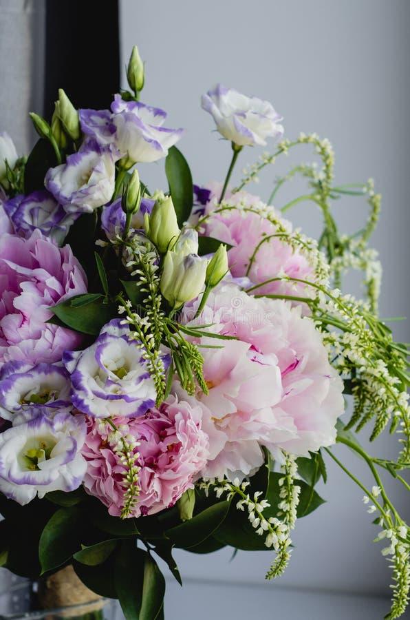 De rijke bos van roze pioenenpioen en lilac eustomarozen bloeit in glasvaas op witte achtergrond Rustieke stijl, nog stock foto's