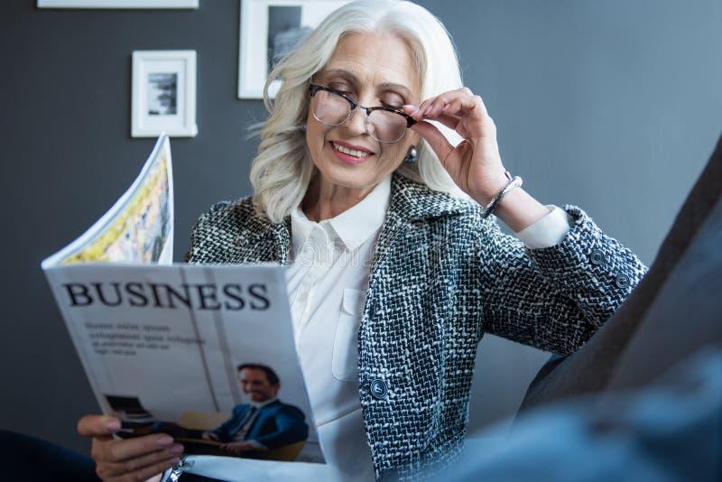 De rijke vrolijke hogere dame houdt tijdschrift royalty-vrije stock fotografie