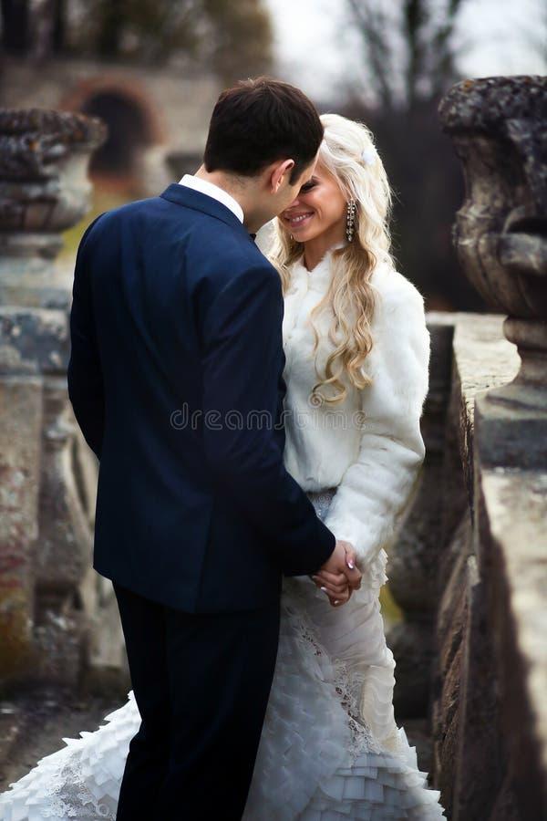 De rijken verzorgen en het van achtergrond bruidhuggingoutdoor muurgras verwarmt a royalty-vrije stock foto