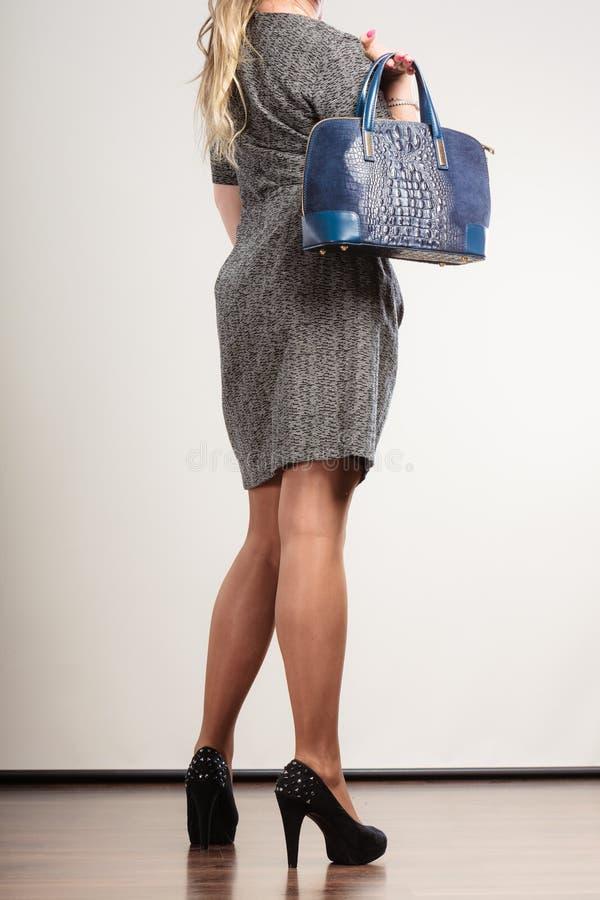 De rijpe bedrijfsvrouw houdt handtas stock foto