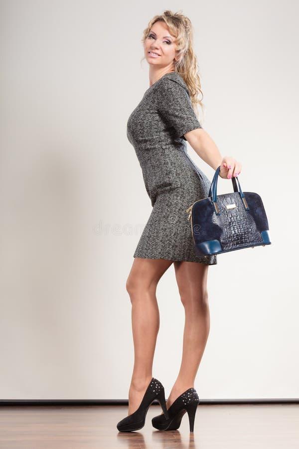 De rijpe bedrijfsvrouw houdt handtas stock afbeeldingen