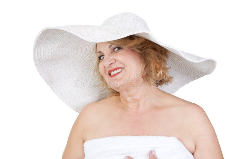 De rijpe dame maakt wellnessvakantie - vrouw die op witte bedelaars wordt geïsoleerd royalty-vrije stock afbeelding