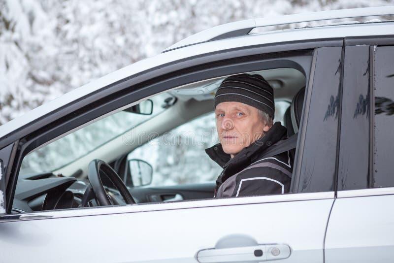 De rijpe Europese mens zit op bestuurderszetel van auto met geopend venster Uren en landschap royalty-vrije stock foto's