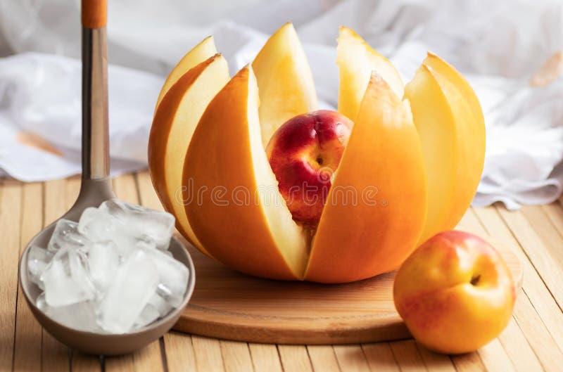 De rijpe gele die meloenbesnoeiing in plakken in de vorm van een bloem met gehele nectarine wordt gevuld is op de keukenlijst Gie royalty-vrije stock afbeeldingen